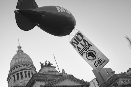 "A sign hangs from a balloon as demonstrators take part in a protest organized by the ""Quebracho"" group outside the Congress building in Buenos Aires, Argentina, on Tuesday, March 15, 2016. Argentine President Mauricio Macri is winning support in Congress for a deal with creditors, ending a 15-year dispute with holdout bondholders and paving the way for new debt sales. Photographer: Diego Levy/Bloomberg via Getty Images"