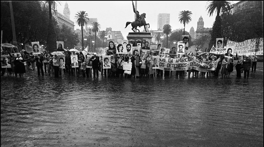 "(FILE) ""Madres de Plaza de Mayo"" remain upright on the flooding square in front of the Presidential Palace, claiming for their missing sons and daughters, circa 1982 in Buenos Aires. The organization will be 30 years next April 30th, 2007. According to human rights organizations about 30.000 people disappeared in Argentina during the military dictatorship, 1976-1983. ""Madres"" members still walk in Plaza de Mayo every Thursday. AFP PHOTO/Daniel GARCIA        (Photo credit should read DANIEL GARCIA/AFP/Getty Images)"