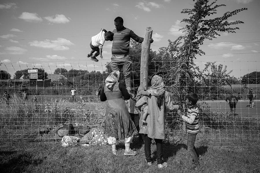 Una familia salta la valla de una autopista en el pueblo de Roszke junto a cientos de personas huyendo de la policia que queria llevarlos a un campo de refugiados. Roszke. Hungria.  Olmo Calvo. 09/09/2015