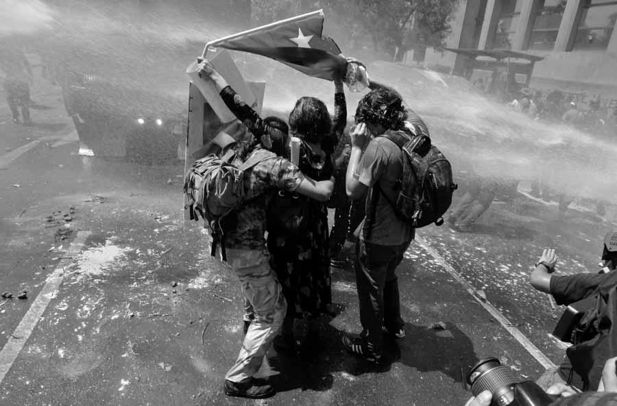 protestas-chile-bandera-camion-hidrante-agua-represion