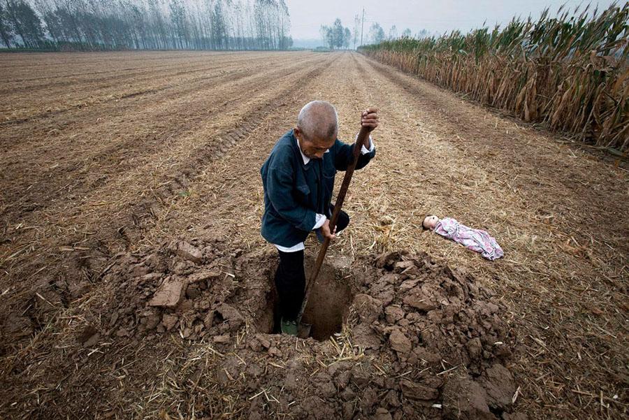 Un granjero cava la tumba para enterrar a un niño hallado muerto, 2010. © Lu Guang