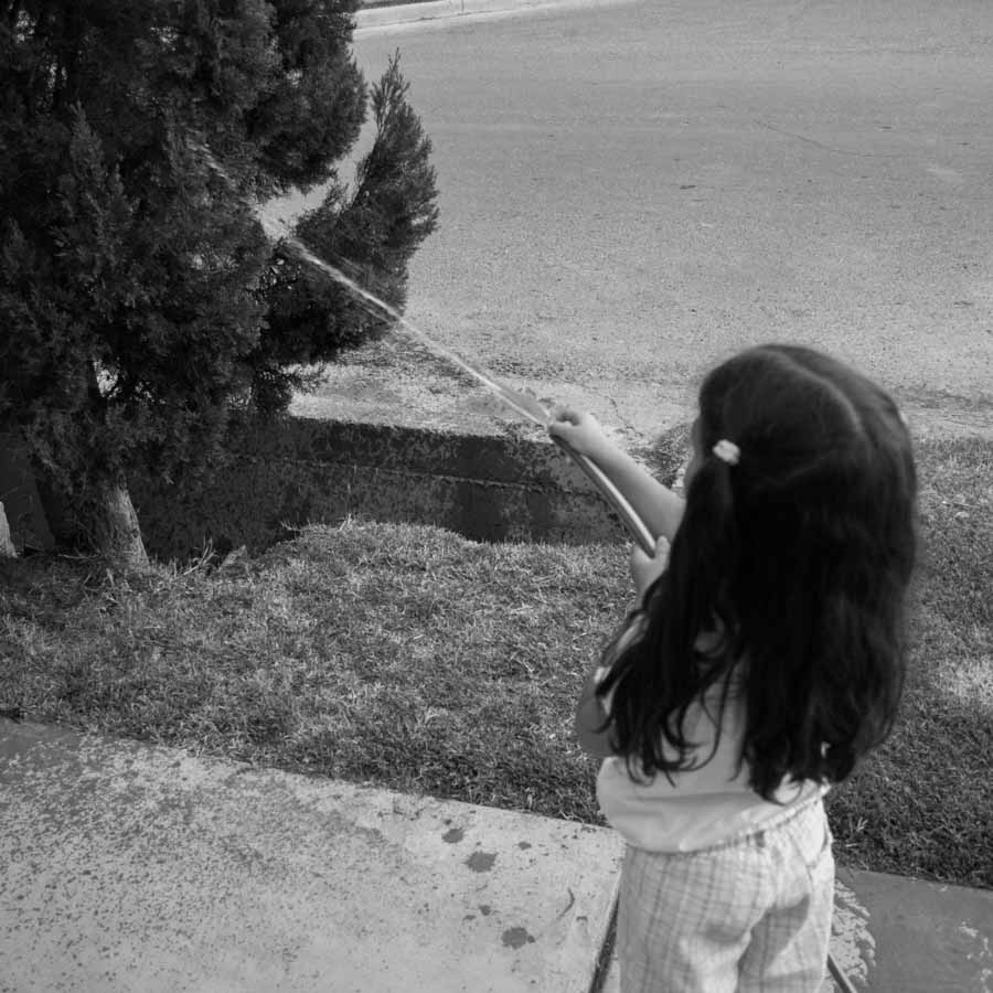 nena-regar-plantas-patio